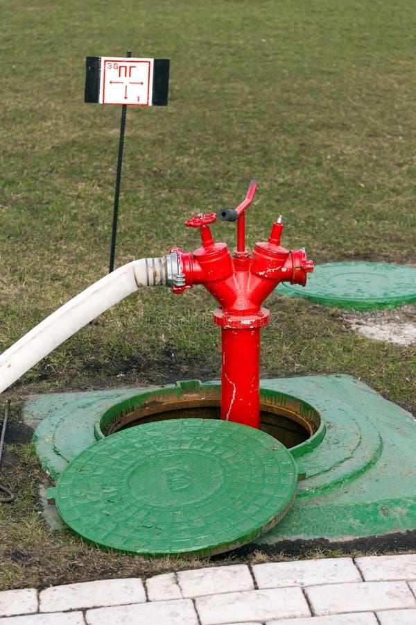 Roter Hydrant steht im Einsteigeloch stockbild