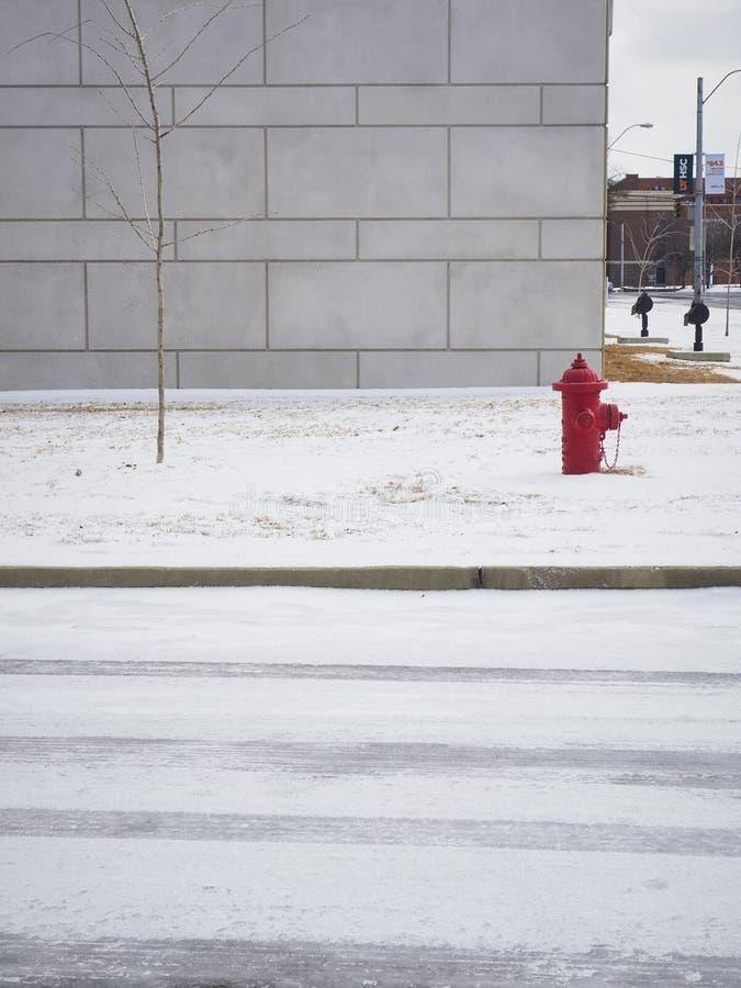 Roter Hydrant vor grauem Gebäude im Schnee lizenzfreies stockbild