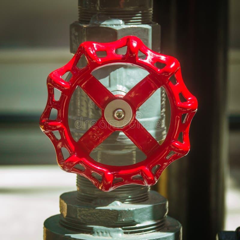 Roter industrieller Ventil-Hahn auf einem Metallrohr in einer Fabrik lizenzfreies stockfoto