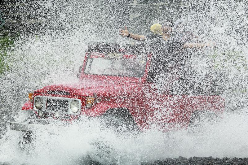 Roter Jeep High Speed Crossing Water stockfotos