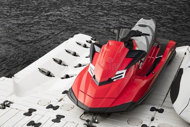 Roter Jet-Ski geparkt neben dem Meer lizenzfreie stockbilder