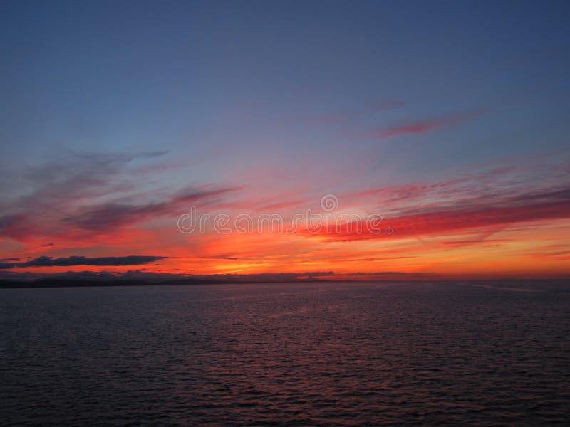 Roter kanadischer Sonnenuntergang, der auf Ozean glitzert stockfotos