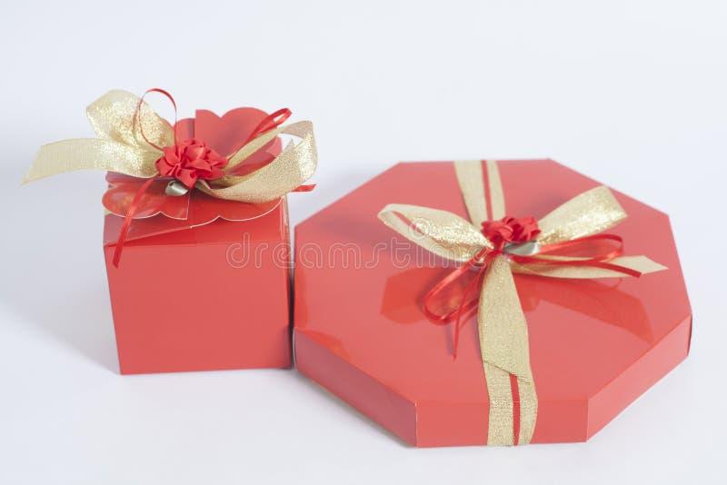 Roter Kasten mit Süßigkeiten und Goldband beugen lizenzfreie stockfotografie
