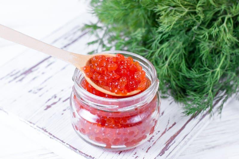 Roter Kaviar in einem Löffel über einem Glasgefäß auf weißem hölzernem Hintergrund lizenzfreies stockbild