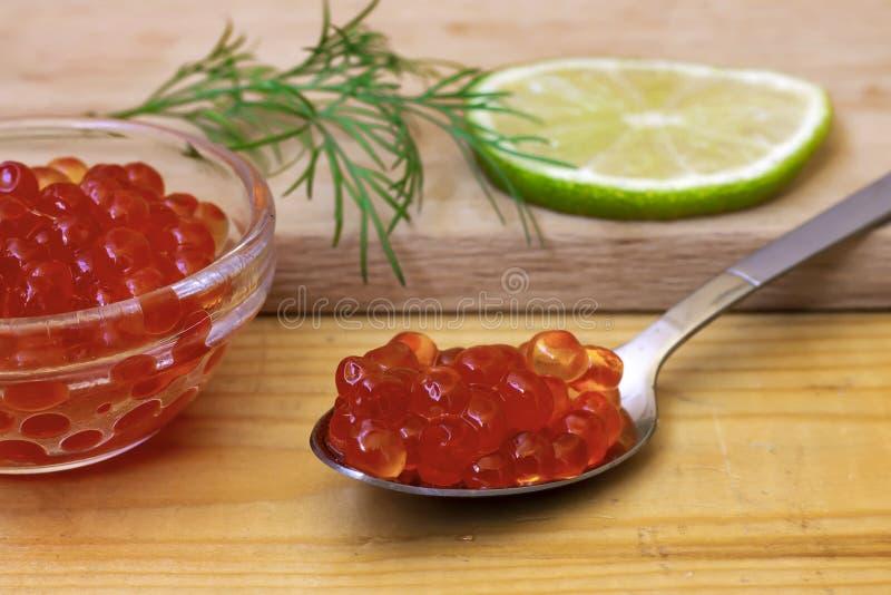 Roter Kaviar liegt in einem Löffel stockfotografie