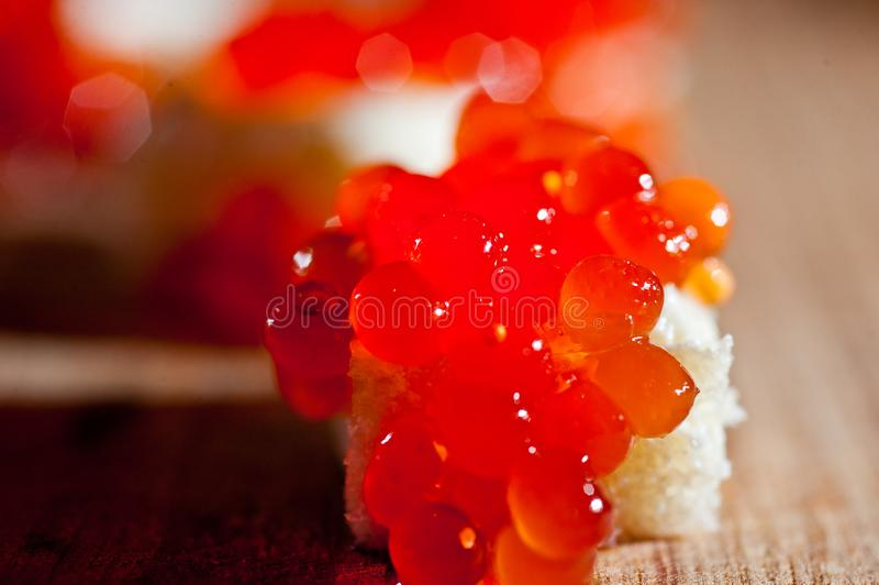 Roter Kaviar mit Brot und Butter auf einem dunklen Hintergrund stockbild