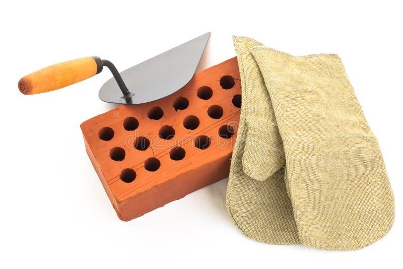 Roter keramischer Ziegelstein, Trowel und Handschuh lizenzfreie stockfotos