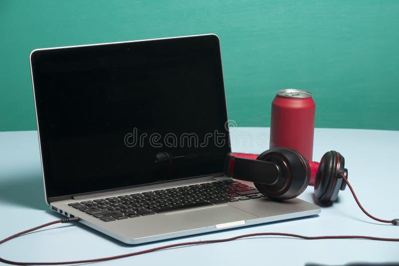 Roter Kopfhörer auf einem Notizbuch mit einem roten Soda lizenzfreies stockfoto