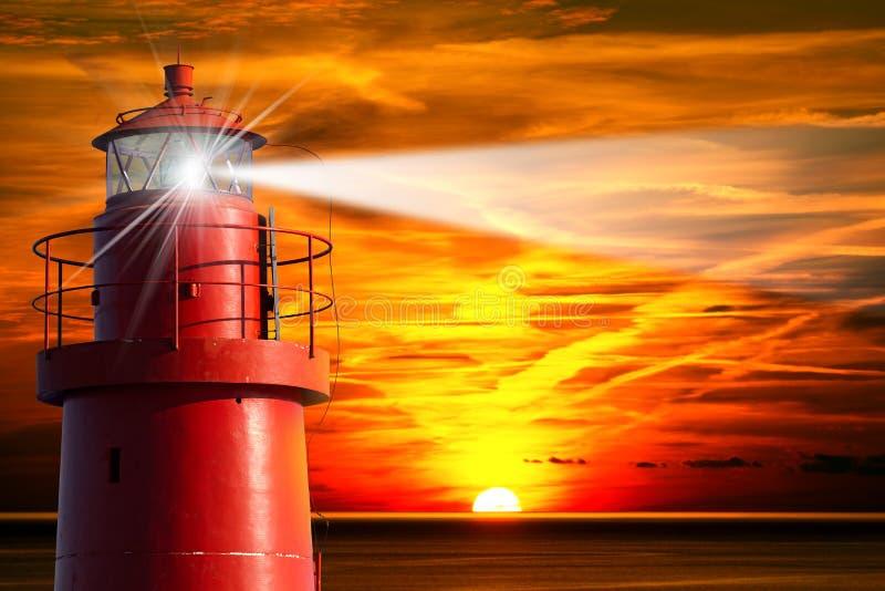 Roter Leuchtturm mit Lichtstrahl bei Sonnenuntergang stockfotos