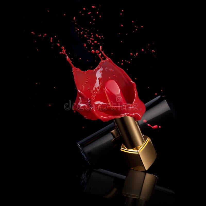 Roter Lippenstift mit Spritzen der Farbe stockfotos