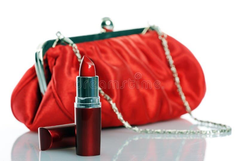 Roter Lippenstift und Geldbeutel stockbild