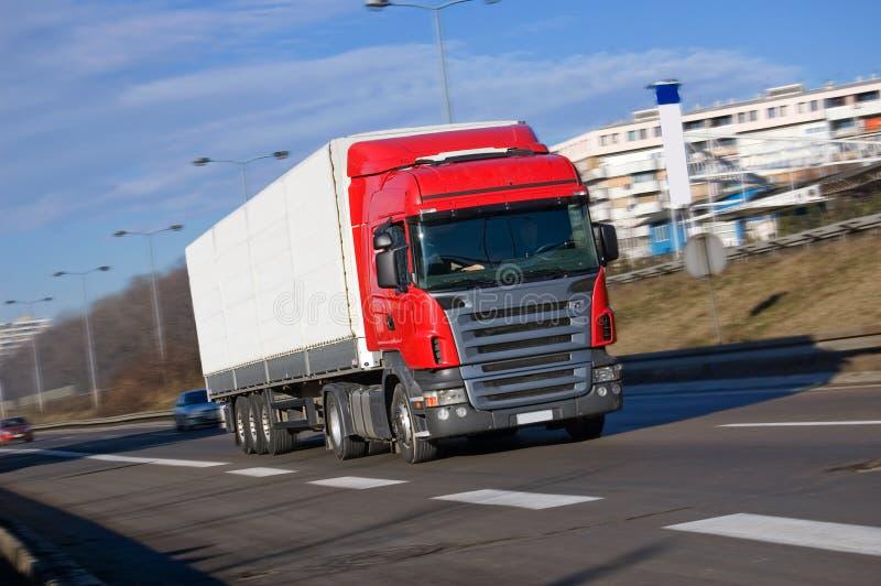 Roter LKW, der schnell antreibt lizenzfreie stockbilder