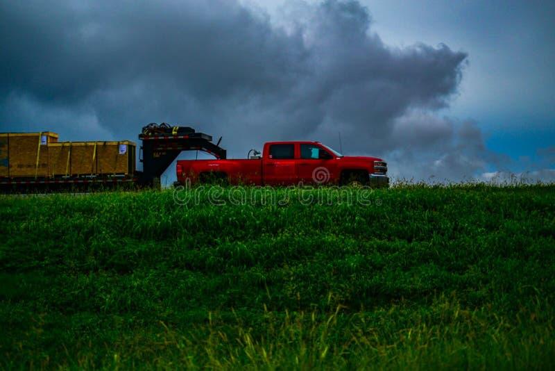 Roter LKW, der Versand gegen graue Wolken schleppt stockfotografie