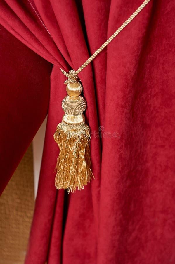 Roter Luxusvorhang mit einer Quaste und einem Seil stockbild