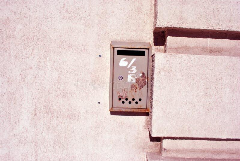 Roter Metallbriefkasten mit der weißen Zahl gemalt auf ihr, horizontaler Hintergrund des strukturierten Wandschmutzes stockfotos