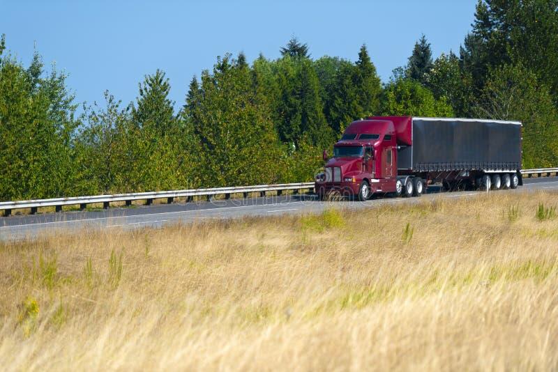 Roter moderner halb LKW und schwarzer Planenanhänger lizenzfreies stockbild