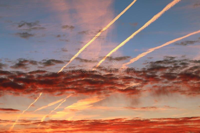 Roter Morgenhimmel und Ströme des verkürzten Dampfes lizenzfreies stockfoto