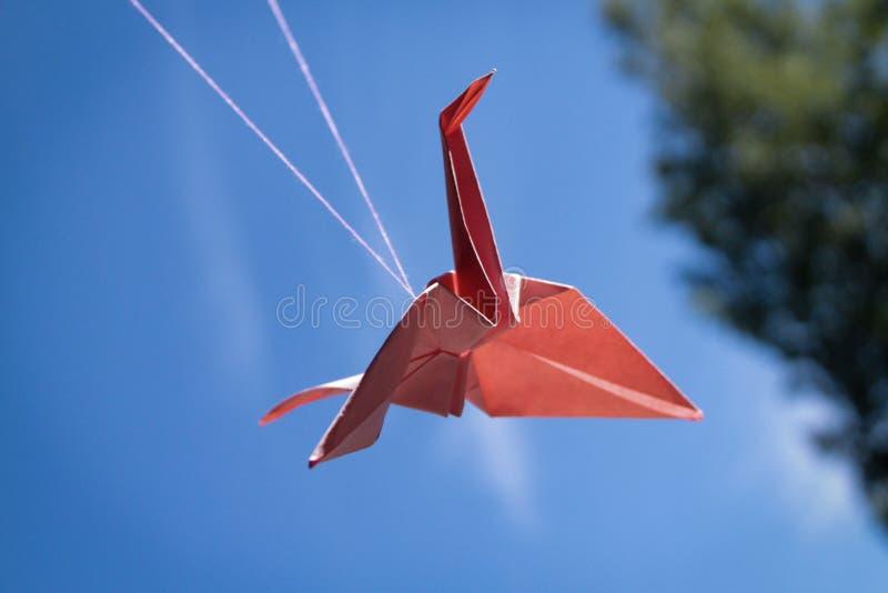 Roter Papiervogelorigami streckt sich auf Himmel lizenzfreies stockfoto