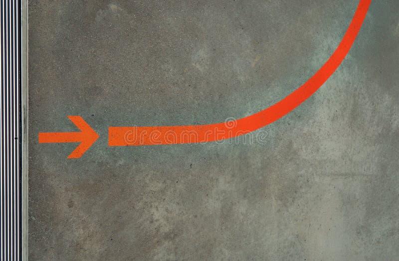 Roter Pfeil als Wegweiser auf grauem, horizontalem Hintergrund lizenzfreies stockbild