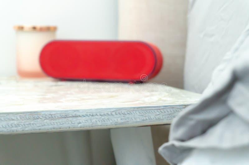 Roter Radiowecker und Kerzenglas auf einem Nachttisch nightstand, wenn dem Bett und Leinen in den weichen Farben zeigen stockbilder