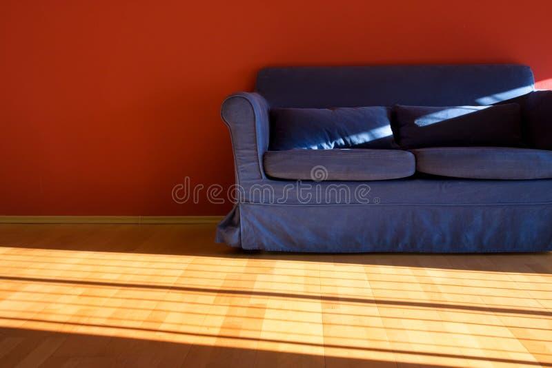 Roter Raum mit blauem Sofa lizenzfreies stockbild