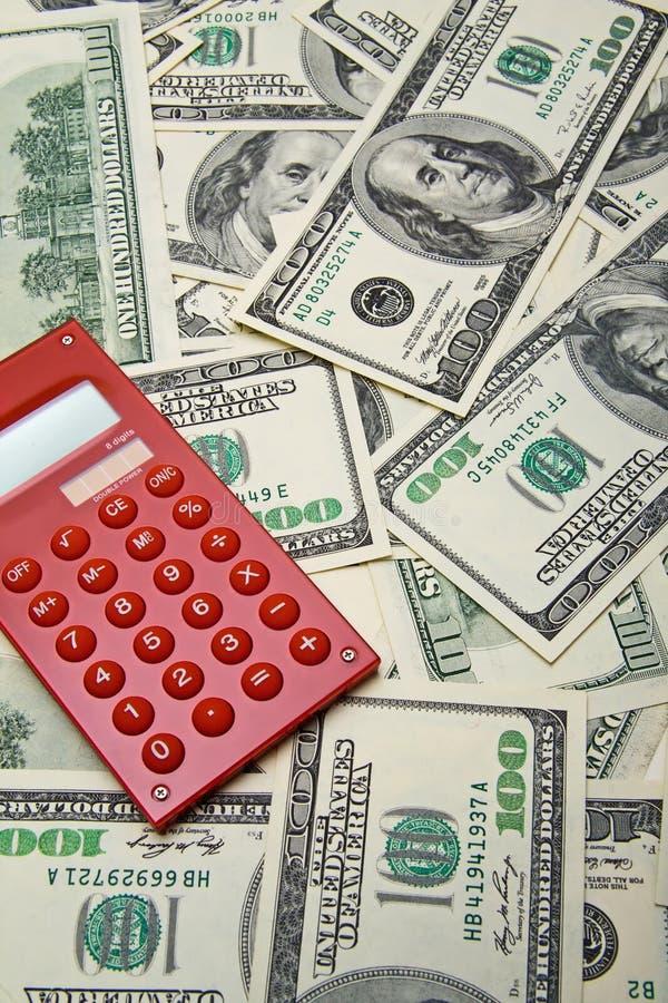 Roter Rechner auf dem Hintergrund mit $100 Banknoten lizenzfreie stockfotos