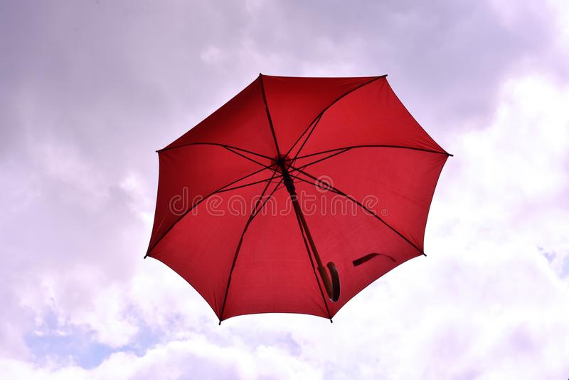 Roter Regenschirm, der in stürmische Himmel schwimmt lizenzfreie stockbilder