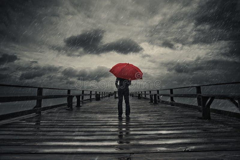 Roter Regenschirm im Sturm stockfotografie
