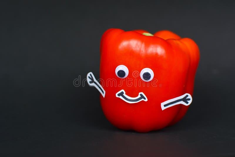 Roter reifer Paprika mit den lustigen Schutzbrillenaugen, Stockhänden und glücklichem lächelndem Mund lokalisiert auf schwarzem H stockfotografie