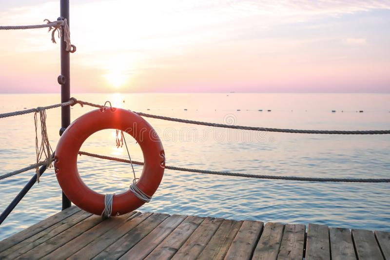 Roter Rettungsgürtel auf hölzernem Pier auf Hintergrund des Meerblicks an der Dämmerung stockbild