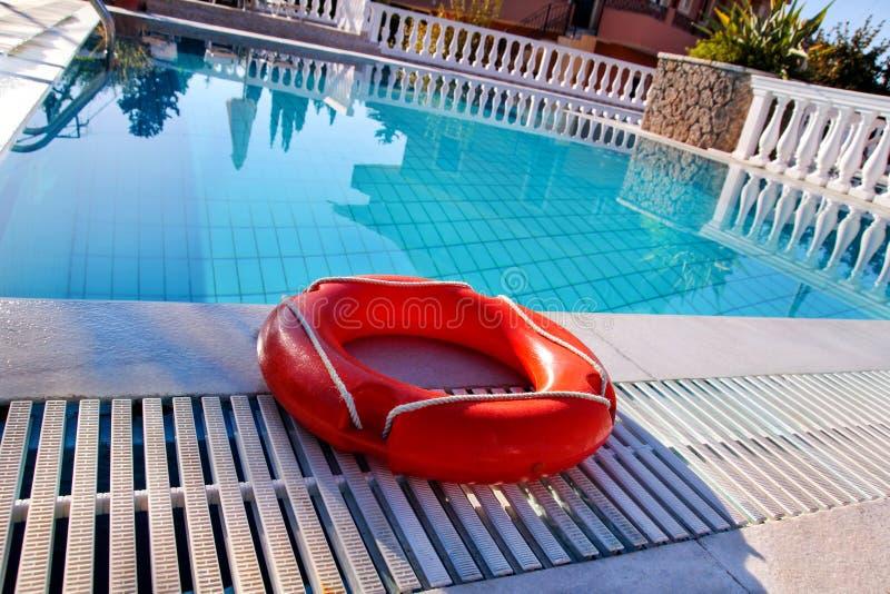 Roter Rettungsringpoolring am Swimmingpool Roter Poolring in kühlem b stockbild