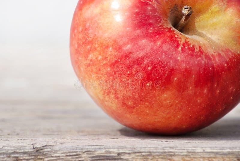 Roter saftiger fester Fruchtapfel unter Sonnenlicht auf einer Tafel gegen eine graue Wand Konzept eines natürlichen Nahrungsbiolo stockbild