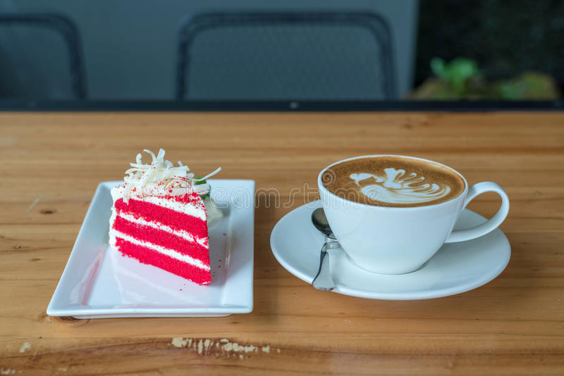 Roter Samtkuchen auf weißer Platte und Kaffeetasse auf Holz lizenzfreie stockfotos