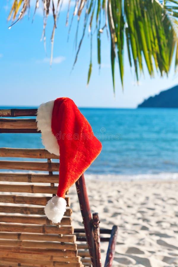 Roter Sankt Hut, der am Strandstuhl hängt lizenzfreies stockbild