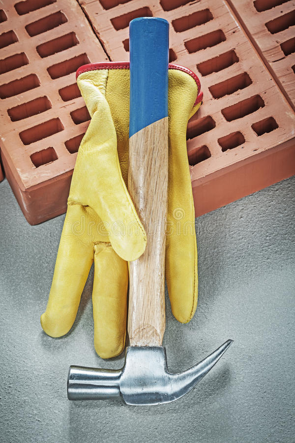 Roter Schutzhandschuhtischlerhammer der Bauziegelsteine auf concret stock abbildung
