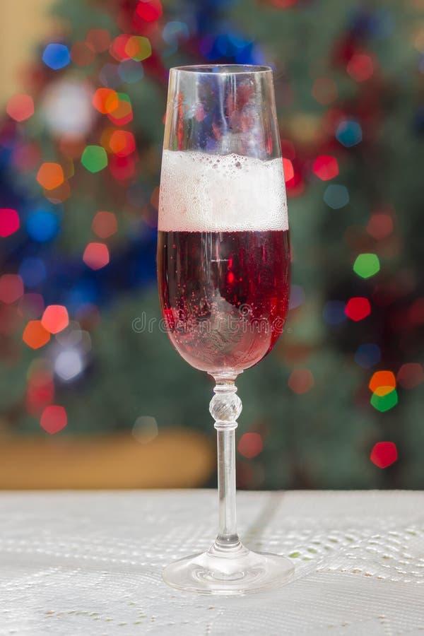 Roter Sekt auf unscharfem Hintergrund von Weihnachtslichtern stockfotografie