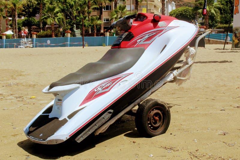 Roter Skijet auf einem Anhänger auf einem sandigen Strand stockbilder