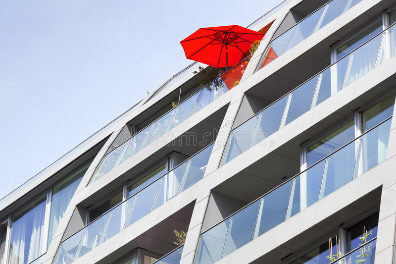 Roter Sonnenschirm auf einem Wohngebäudebalkon lizenzfreie stockfotos