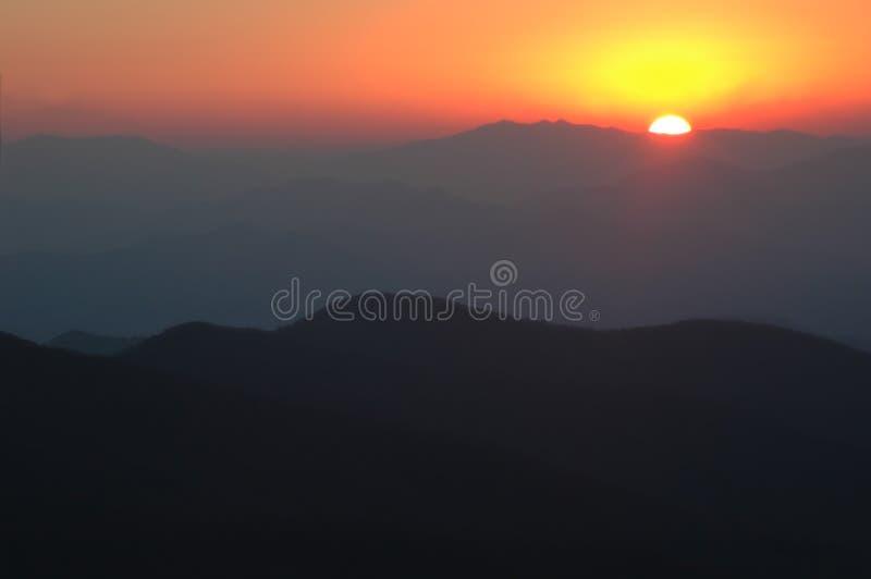 Roter Sonnenuntergang über rauchigen Bergen lizenzfreie stockfotografie