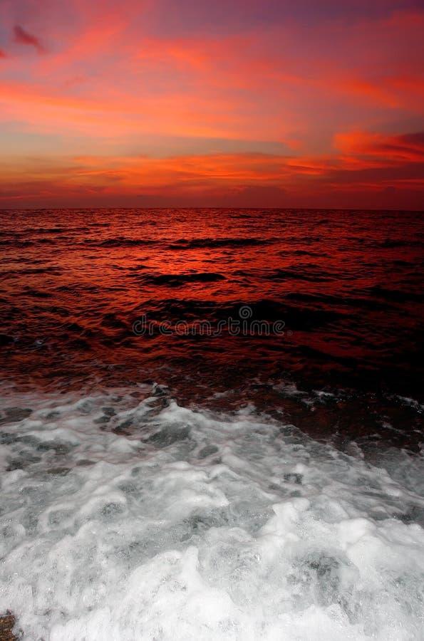Roter Sonnenuntergang mit dem Brechen des Wassers. lizenzfreie stockfotografie