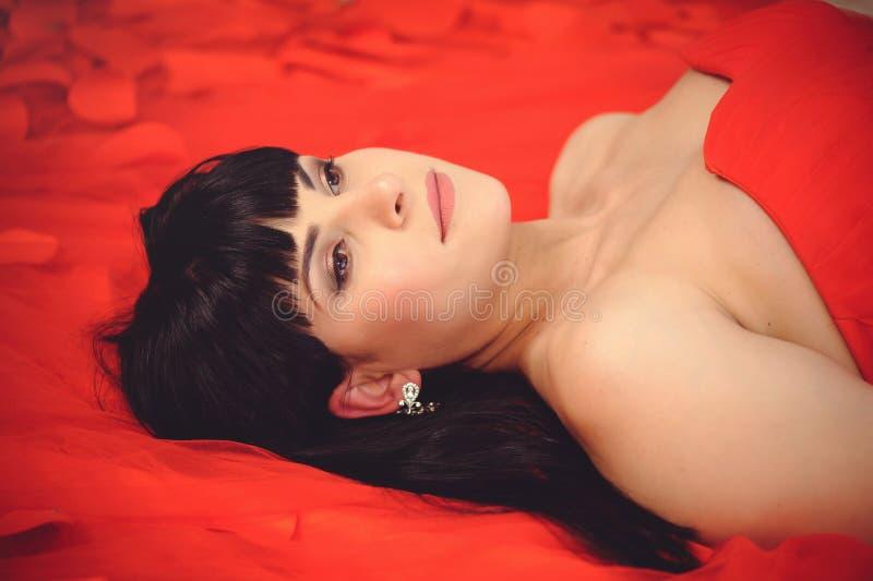 Roter Tag Liebendes Mädchen das Mädchen in einem roten Kleid liegt auf einem roten Hintergrund Hintergrund vom hellen Gewebe Rote lizenzfreie stockbilder