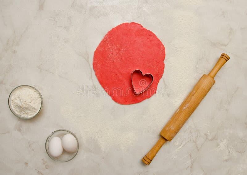 Roter Teig mit einem herausgeschnittenen Herzen, einem Nudelholz, Eiern und einem Mehl auf einer weißen Tabelle Draufsicht, Raum  stockfoto
