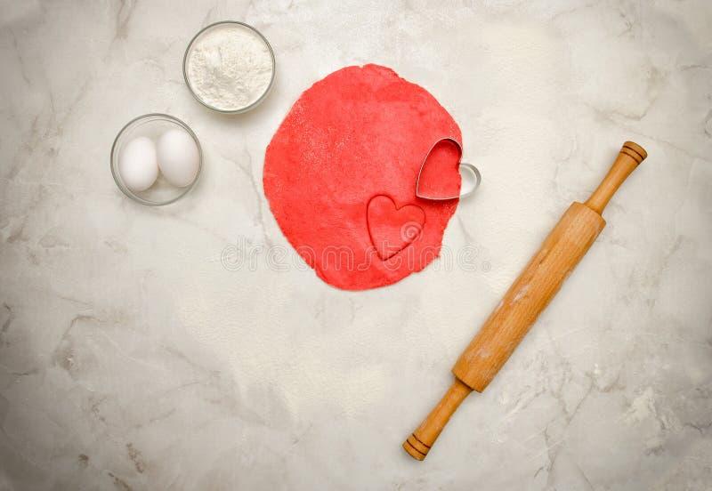 Roter Teig mit einem herausgeschnittenen Herzen, einem Nudelholz, Eiern und einem Mehl auf einer weißen Tabelle Draufsicht, Raum  lizenzfreie stockfotografie