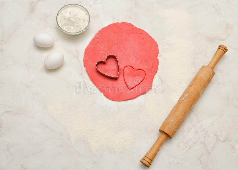 Roter Teig mit einem herausgeschnittenen Herzen, einem Nudelholz, Eiern und einem Mehl auf einer weißen Tabelle Draufsicht, Raum  lizenzfreies stockfoto