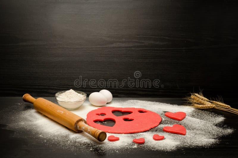 Roter Teig mit geschnitzten Herzen auf einer schwarzen Tabelle Nudelholz, Mehl, Eier und Weizenähren Platz für Text lizenzfreie stockbilder