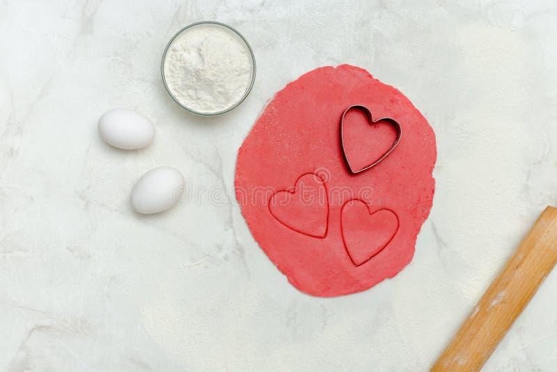 Roter Teig mit herausgeschnittene Herzen, Eier, Mehl und Nudelholz, an stockbild