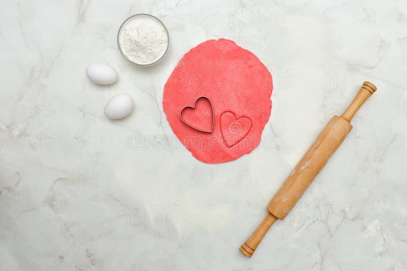 Roter Teig mit herausgeschnittene Herzen, Eier, Mehl und Nudelholz, an lizenzfreies stockfoto