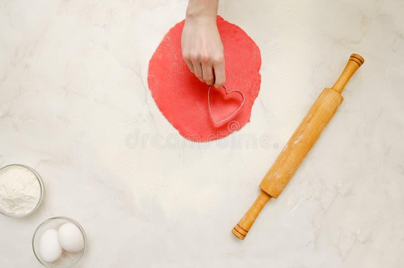 Roter Teig Plast, eine weibliche Hand mit einer Form für den Schnitt des Herzens Nudelholz, Eier und Mehl auf einer weißen Tabell stockfoto