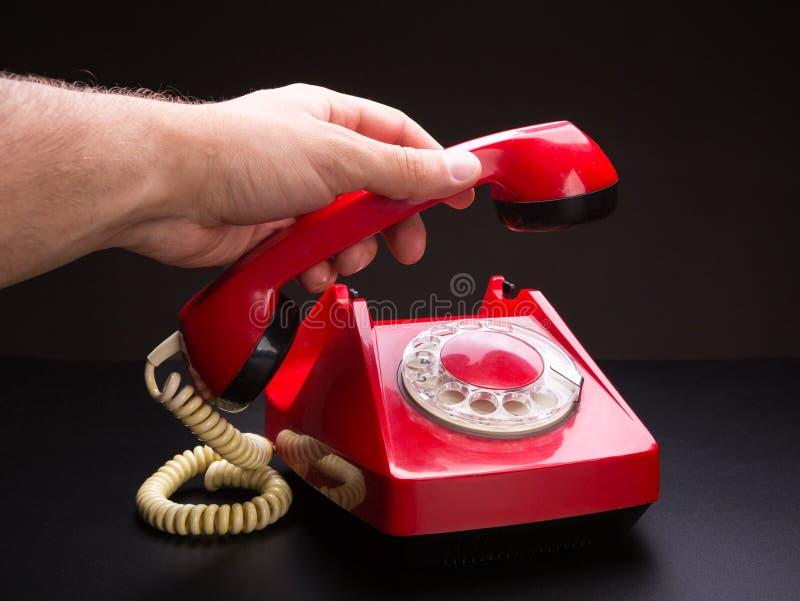 Roter Telefonhörer in der Hand stockfoto