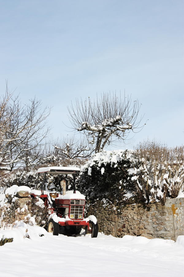 Roter Traktor im Schnee lizenzfreie stockfotografie